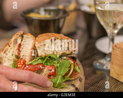 Creative Tight Cropped Image of a Vegetarian Roast Pepper Ciabatta Bread Sandwich or Roll And White Wine - Stock Photo
