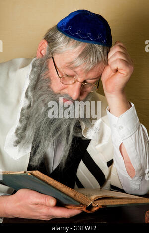Old jewish man with beard reading a book - Stock Photo
