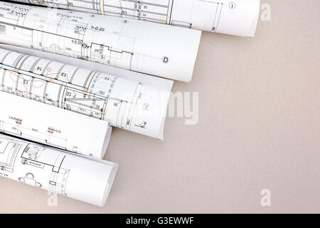 Rolled house blueprints on gray background 3d illustration stock rolls of architecture blueprints and house plans on the desk stock photo malvernweather Images