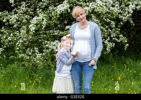 Young pregnant woman and her daughter in the park - Stock Photo