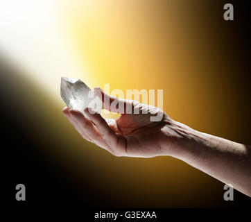 Male hand holding large clear terminated crystal quartz wand in a shaft of white and golden light on a black background - Stock Photo