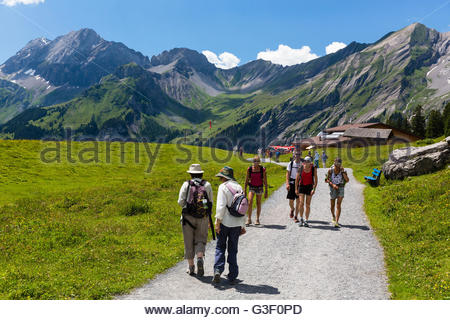 Hikers in front of mountain landscape of Kandersteg on the way from the cable car to the Oeschinensee, Aletsch Jungfrau - Stock Photo