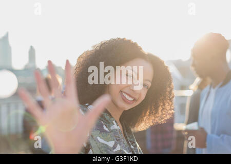 Portrait smiling woman waving at rooftop party - Stock Photo