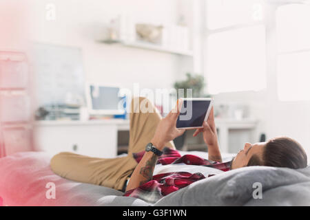 Young man using digital tablet on bed - Stock Photo