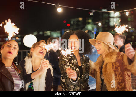 Young women with sparklers at rooftop party - Stock Photo