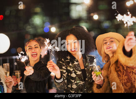 Portrait enthusiastic young women waving sparklers at party - Stock Photo