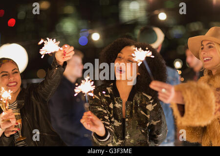 Young women waving sparklers at rooftop party - Stock Photo