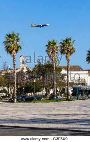 Palm trees in front of the citry gate Arco da Villa with landing airplane, Faro, Algarve, Portugal - Stock Photo