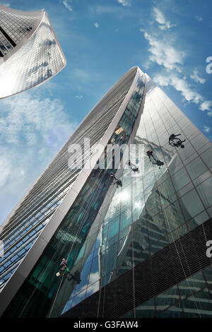Moscow, Russia - June 10, 2016: Cleaning windows on the side of a high rise building. Moscow City. View of skyscrapers - Stock Photo