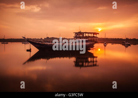 Sunrise mirror reflection on water of an old wooden shipwreck an industrial boat abandoned in the sea on the beautiful - Stock Photo
