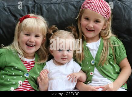 Blonde Children, kids, girls, sisters cuddling together laughing and smiling  family fun, togetherness concept, - Stock Photo