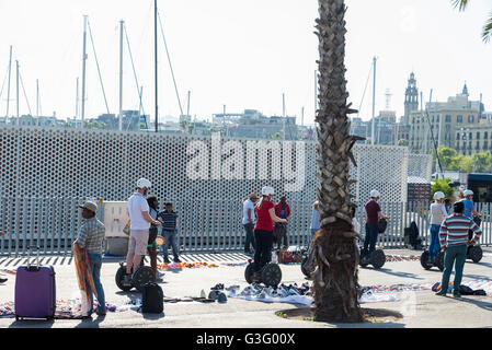 Tourists on a Segway in the seafront promenade full of tourists and with a flea market in Barcelona, Catalonia, - Stock Photo