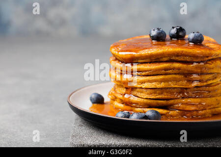 Pumpkin pancakes with maple syrup and blueberries - Stock Photo