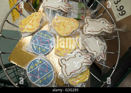 Wrapped Easter egg, chick and rabbit cookies in grocery store checkout line basket. St Paul Minnesota MN USA - Stock Photo
