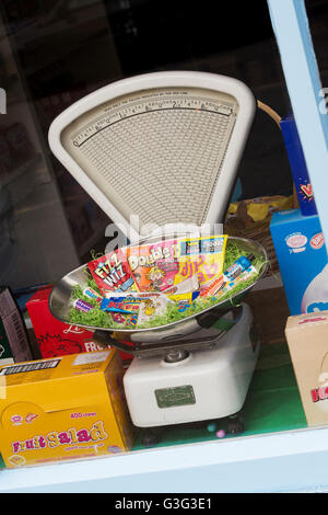 Old vintage weighing scales and childrens sweets in a sweet shop window. Tetbury. Cotswolds, Gloucestershire, England - Stock Photo