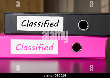 Bright office folders over dark background and classified text concept - Stock Photo