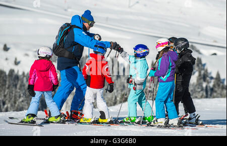 A ski instructor teaches a group of children in the French ski resort of Courchevel. - Stock Photo