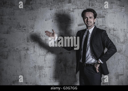 Portrait of a businessman in suit showing to empty space over concrete wall background - Stock Photo