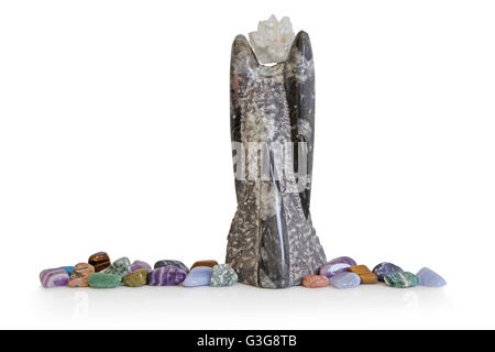 Large Angel shaped fossil topped with apothyllite cluster to form head and of tumbled crystals at the base on white - Stock Photo
