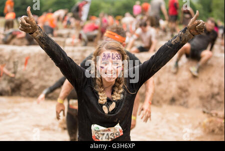 Tough Mudder girl finishes the Mud Mile part of the obstacle course Drumlanrig Castle, Dumfries and Galloway, Scotland, - Stock Photo