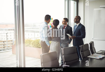 Diverse multiracial management team standing grouped in front of a large bright window in the conference room discussing - Stock Photo