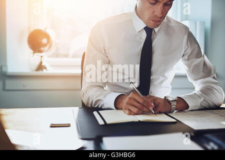 Close up of business man in shirt and tie working in his office writing in a classic note book - Stock Photo