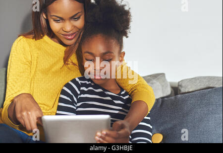 Black mom and daughter learning on tablet sitting at home in sofa - Stock Photo