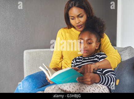 Mom and daughter reading a book looking excited reading - Stock Photo