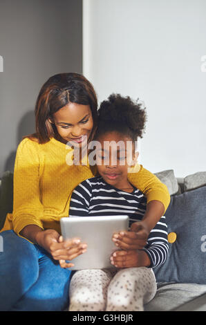 Little black girl and mom with tablet sitting in sofa smiling