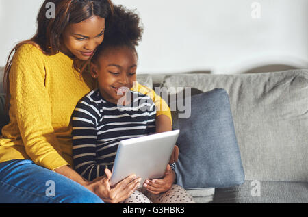 Black mom and child with tablet having a good time smiling and learning