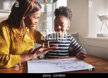 Mom learning daughter to calculate getting ready for school, black family