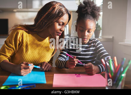 Mom and child drawing in kitchen, black mother and daughter - Stock Photo
