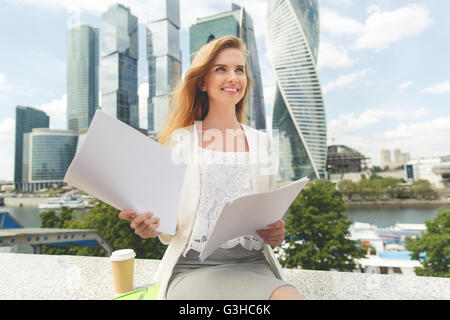 business, paperwork and people concept - young smiling businesswoman with heap of papers sitting on city bench - Stock Photo