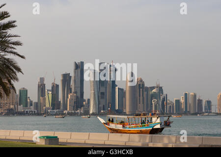 Doha West bay viewed from Al Corniche. Dhow boat with Qatari women in Abayas in the foreground. - Stock Photo