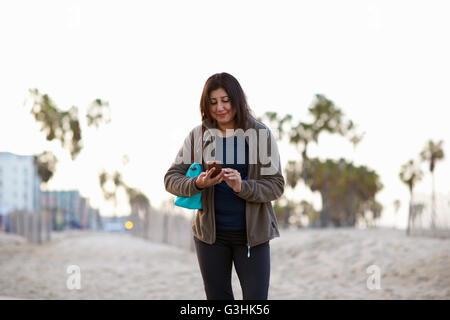 Woman carrying handbag looking down at smartphone smiling - Stock Photo