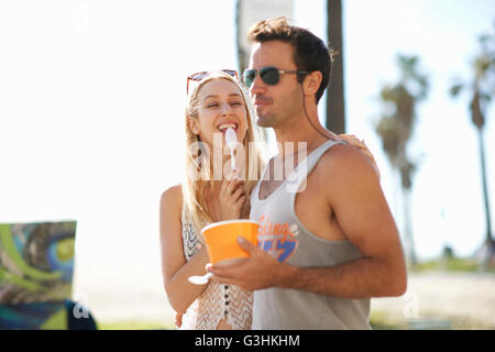 Couple strolling and eating frozen yoghurt at Venice Beach, California, USA - Stock Photo