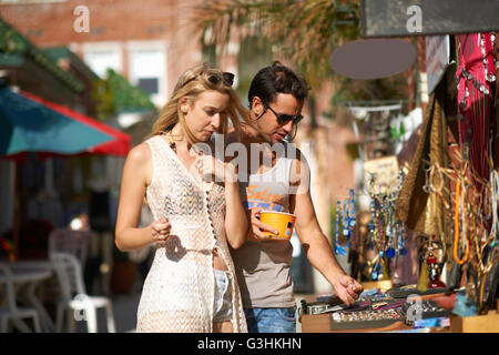 Couple eating frozen yoghurt and browsing jewellery stall at Venice Beach, California, USA - Stock Photo