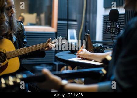 Two musicians in music studio, writing music - Stock Photo