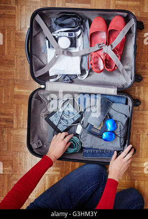 Woman packing suitcase, overhead view - Stock Photo
