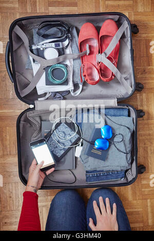 Woman packing suitcase, holding smartphone, overhead view - Stock Photo