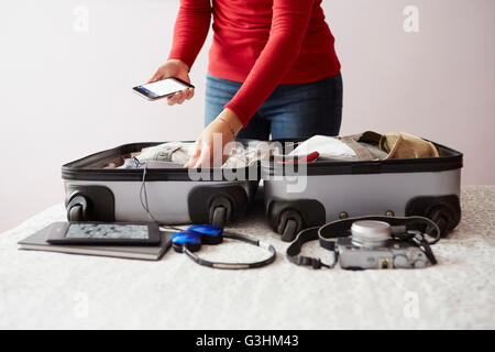 Woman packing suitcase, holding smartphone, mid section - Stock Photo