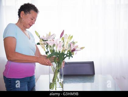 Senior woman arranging vase of flowers - Stock Photo