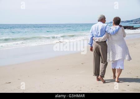 Senior couple waking on beach, rear view Stock Photo
