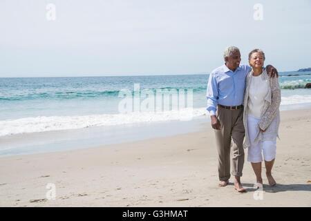 Senior couple waking together on beach, smiling Stock Photo