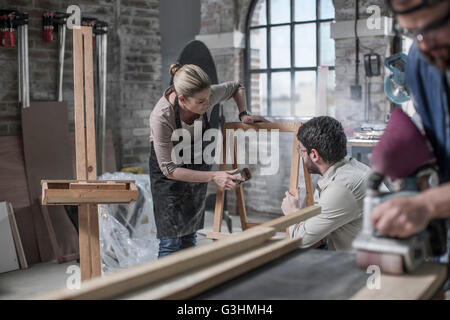 Carpenter team sanding wood in antique restoration workshop - Stock Photo