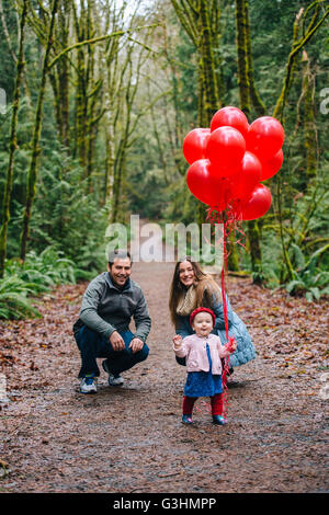 Portrait of parents crouching toddler daughter holding a bunch of red balloons in forest - Stock Photo