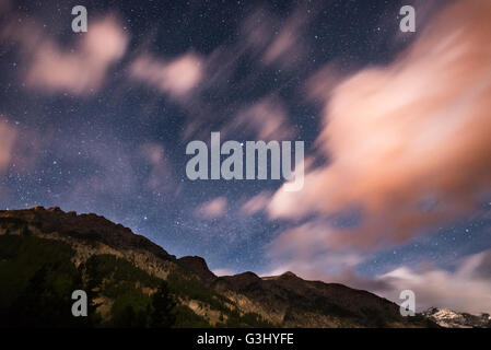 The starry sky with blurred motion colorful clouds and bright moonlight. Expansive night landscape in the European - Stock Photo