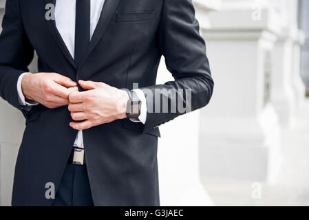 Pleasant business man holding his jacket - Stock Photo