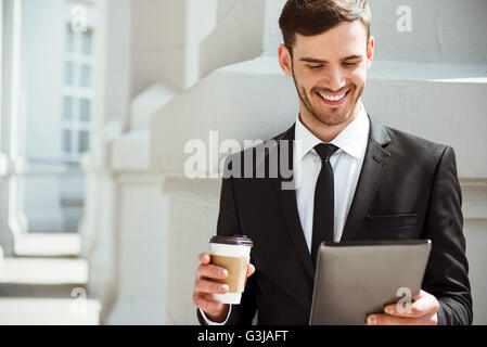 Positive content man using tablet - Stock Photo