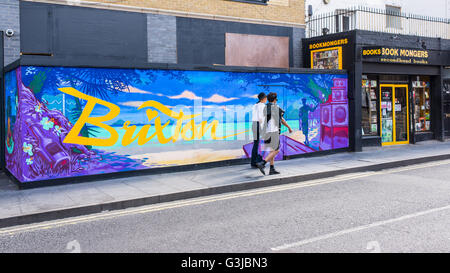 Hipster couple walking in front of mural graffiti with the word Brixton written on a background with tropical beach - Stock Photo